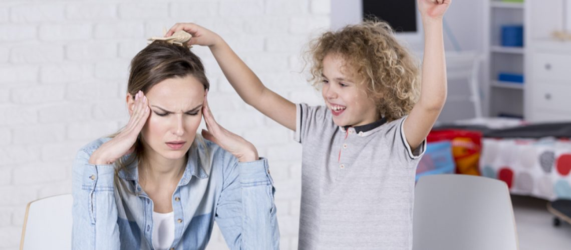 Child annoying his tired mother with headache